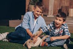 Muchachos que juegan con el perrito lindo de Labrador junto Foto de archivo libre de regalías