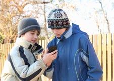 Muchachos que juegan con el teléfono de mobil Imagen de archivo