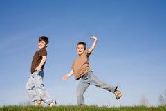 Muchachos que juegan en una colina Fotografía de archivo libre de regalías
