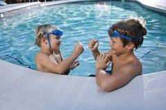 Muchachos que juegan a juegos en el borde de la piscina Fotos de archivo