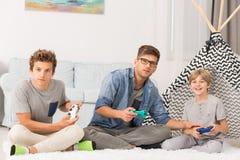Muchachos que juegan a los videojuegos con el papá Fotos de archivo