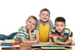 Muchachos que leen en el piso Foto de archivo