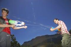 Muchachos que luchan con los armas de agua en montañas Foto de archivo