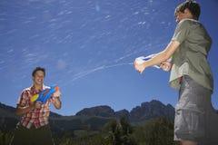 Muchachos que luchan con los armas de agua en montañas Imagen de archivo libre de regalías