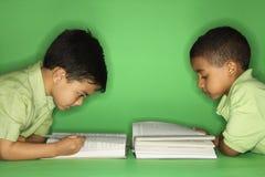 Muchachos que mienten y que leen. Foto de archivo libre de regalías
