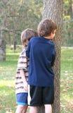 Muchachos que miran a escondidas alrededor de árbol Foto de archivo libre de regalías