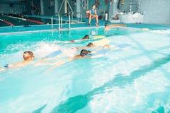Muchachos que nadan con el tablón en una raza de la piscina Foto de archivo