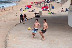 Muchachos que pagan fútbol de la playa cerca del embarcadero y del faro del milenio en las rocas de Umhlanga Imagen de archivo