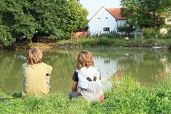 Muchachos que pescan en la charca Imagen de archivo