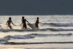 Muchachos que se divierten el practicar surf en la puesta del sol Imagenes de archivo