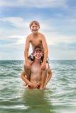 Muchachos que se divierten en el mar claro hermoso imágenes de archivo libres de regalías