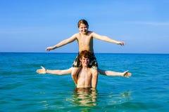 Muchachos que se divierten que juega a cuestas en el océano caliente Imágenes de archivo libres de regalías