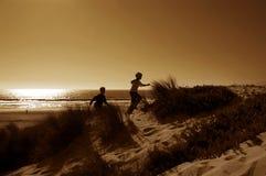 Muchachos que se ejecutan en dunas Imagen de archivo libre de regalías