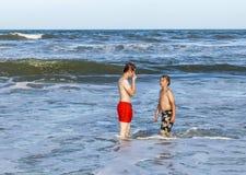 Muchachos que se relajan en la playa Imágenes de archivo libres de regalías