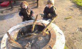 Muchachos que se sientan alrededor de hoyo del fuego del campo Fotos de archivo libres de regalías