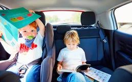 Muchachos que se sientan en el asiento trasero, libro de lectura mientras que viaja en el coche foto de archivo libre de regalías