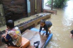 Muchachos que se sientan en un barco en la inundación Foto de archivo libre de regalías