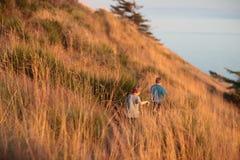 Muchachos que van de excursión en una colina al lado del océano fotos de archivo libres de regalías