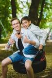 Muchachos sonrientes que se divierten en el patio Niños que juegan al aire libre en verano Adolescentes que montan en un oscilaci Fotografía de archivo