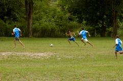 Muchachos tailandeses jovenes que juegan al juego de fútbol Foto de archivo libre de regalías