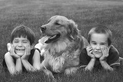 Muchachos y el perro Imagen de archivo