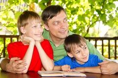 Muchachos y lectura del papá Fotos de archivo