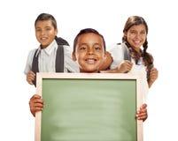 Muchachos y muchacha hispánicos sonrientes en el blanco que lleva a cabo el tablero de tiza en blanco Imagen de archivo libre de regalías