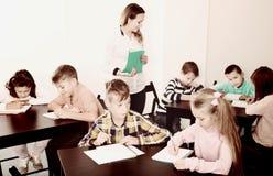 Muchachos y muchachas con el dibujo del profesor Imágenes de archivo libres de regalías