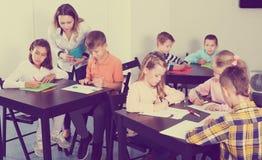 Muchachos y muchachas con el dibujo del profesor Fotografía de archivo libre de regalías