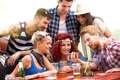 Muchachos y muchachas en comida campestre en la naturaleza que se divierte mientras que mira las fotos en el teléfono móvil imagen de archivo libre de regalías