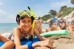 Muchachos y muchachas en máscaras del equipo de submarinismo en la playa Foto de archivo