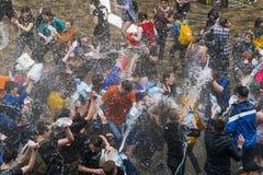 Muchachos y muchachas felices que vierten el agua en uno a Foto de archivo