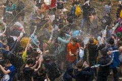 Muchachos y muchachas felices que vierten el agua en uno a Imágenes de archivo libres de regalías