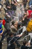 Muchachos y muchachas felices que vierten el agua en uno a Fotografía de archivo
