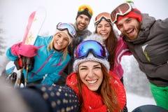 Muchachos y muchachas junto en el esquí Imagen de archivo libre de regalías