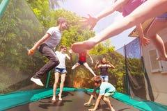 Muchachos y muchachas que juegan en el trampolín al aire libre imagen de archivo