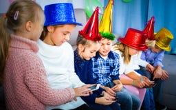 Muchachos y muchachas que pasan el tiempo que juega con smartphones Fotografía de archivo libre de regalías