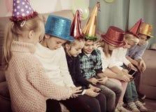 Muchachos y muchachas que pasan el tiempo que juega con smartphones Imagen de archivo libre de regalías