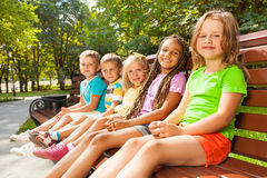 Muchachos y muchachas que se sientan en el banco en parque Fotos de archivo libres de regalías
