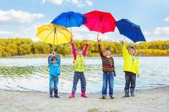 Muchachos y muchachas que sostienen los paraguas Fotografía de archivo libre de regalías