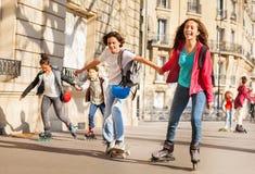 Muchachos y muchachas rollerblading celebrando las manos en la ciudad Imagenes de archivo