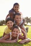 Muchachos y muchachas sonrientes que mienten en una pila en hierba en verano Imagenes de archivo