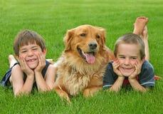 Muchachos y perro perdiguero de oro Foto de archivo libre de regalías