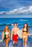 Muchachos y personas que practica surf adolescentes de las muchachas que salen de la playa Imagen de archivo