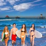 Muchachos y personas que practica surf adolescentes de las muchachas que salen de la playa Fotografía de archivo