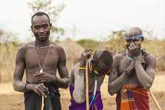 Muchachos y un hombre de la tribu de Mursi con las lanzas en el pueblo de Mirobey Fotos de archivo libres de regalías