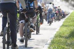 Muchas bicis que compiten con Un grupo de ciclistas que montan durante la calle Fotografía de archivo libre de regalías