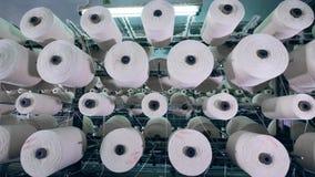 Muchas bobinas encanillan la fibra en una instalación moderna de materia textil metrajes