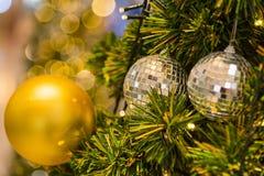 Muchas bolas de espejo adornan en árbol verde de las hojas y sistema de la iluminación Foto de archivo