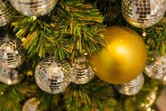 Muchas bolas de espejo adornan en árbol verde de las hojas y sistema de la iluminación Foto de archivo libre de regalías